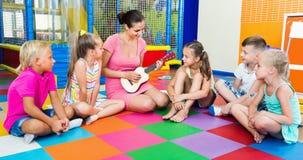 Enfants s'asseyant avec le professeur et écoutant la musique dans la classe Photos stock