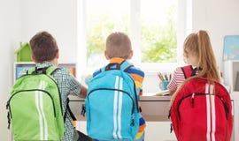 Enfants s'asseyant dans la chambre avec des livres et des sacs à dos Photographie stock libre de droits