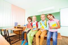 Enfants s'asseyant dans la rangée sur le bureau avec des manuels Image stock