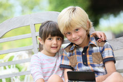 Enfants s'asseyant dans le jardin jouant des jeux Photo libre de droits