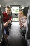 Enfants s'asseyant dans un autobus scolaire Photographie stock libre de droits