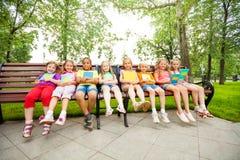 Enfants s'asseyant dans une rangée sur le banc avec des carnets Image stock