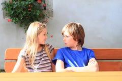 Enfants s'asseyant derrière la table en bois Photographie stock