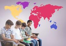 Enfants s'asseyant devant la carte colorée du monde Image libre de droits
