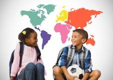 Enfants s'asseyant devant la carte colorée du monde avec le football Image stock