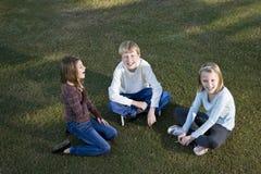 Enfants s'asseyant en cercle sur parler d'herbe Photos libres de droits
