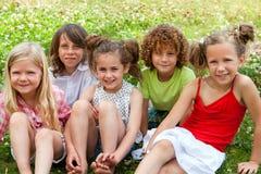Enfants s'asseyant ensemble dans le domaine de fleur. Image stock