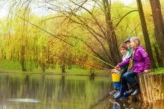 Enfants s'asseyant et pêchant ensemble près de l'étang Photo libre de droits