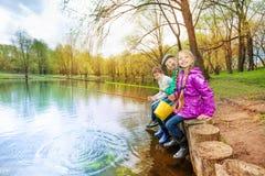 Enfants s'asseyant près de l'étang tenant des articles de pêche Photos stock