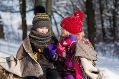 Enfants s'asseyant sous le plaid dans la forêt de neige Photographie stock libre de droits