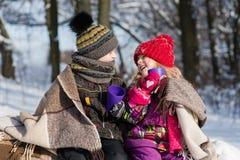 Enfants s'asseyant sous le plaid dans la forêt de neige Photographie stock