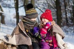 Enfants s'asseyant sous le plaid dans la forêt de neige Image stock