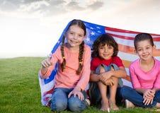 Enfants s'asseyant sous les drapeaux américains dans le domaine Photos stock