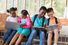 Enfants s'asseyant sur l'escalier utilisant l'ordinateur portable et le comprimé numérique Photographie stock libre de droits