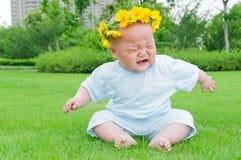 Enfants s'asseyant sur l'herbe pour pleurer image stock