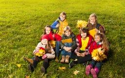 Enfants s'asseyant sur la pelouse Photos stock