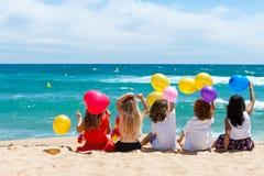 Enfants s'asseyant sur la plage avec des ballons de couleur. Photo libre de droits