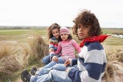Enfants s'asseyant sur la plage de l'hiver image stock