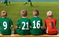 Enfants s'asseyant sur le banc en bois du football du football Enfants Junior Football Team photos stock
