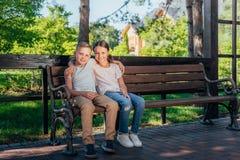 Enfants s'asseyant sur le banc en parc Images stock