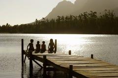 Enfants s'asseyant sur le bord de la jetée au coucher du soleil Photos libres de droits