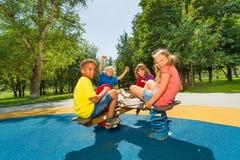 Enfants s'asseyant sur le carrousel de terrain de jeu ensemble Images stock
