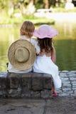 Enfants s'asseyant sur le côté du lac Image libre de droits