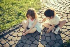Enfants s'asseyant sur le passage couvert en pierre photos stock