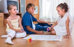 Enfants s'asseyant sur le plancher avec le jeu Photos stock