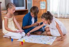 Enfants s'asseyant sur le plancher avec le jeu Photographie stock