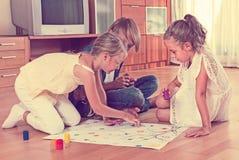 Enfants s'asseyant sur le plancher avec le jeu Images libres de droits
