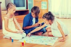 Enfants s'asseyant sur le plancher avec le jeu Photo stock