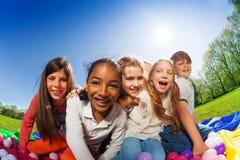 Enfants s'asseyant sur le tapis entouré par les boules colorées Images stock
