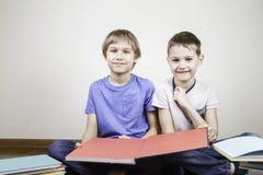 Enfants s'asseyant sur les livres de plancher et de lecture à la maison Images libres de droits
