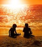 Enfants s'asseyant sur une plage Photo libre de droits
