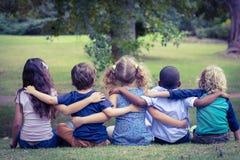 Enfants s'asseyants tournés par dos en parc Photographie stock libre de droits