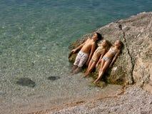 Enfants s'exposant au soleil en mer   Photos stock