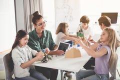 Enfants satisfaisants et adultes faisant les jouets modernes Photos stock