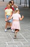 Enfants sautant le jeu de marelle Image libre de droits