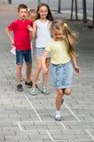 Enfants sautant le jeu de marelle Photos libres de droits