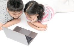Enfants se couchant et bande dessinée de observation sur l'ordinateur portable Photo stock
