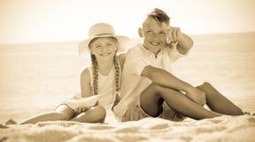 Enfants se dirigeant avec le doigt sur la plage sablonneuse Photos stock