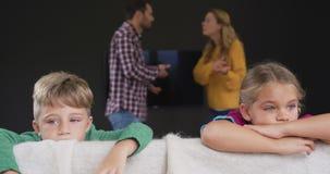 Enfants se penchant sur le sofa tandis que parents discutant à l'arrière-plan à la maison 4k banque de vidéos