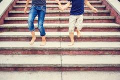 Enfants se précipitant vers le bas sur des escaliers nu-pieds Images stock