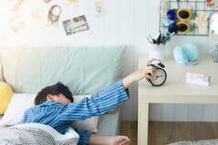 Enfants se réveillant à un réveil dans la chambre à coucher photographie stock