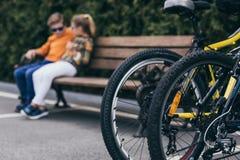 Enfants se reposant sur le banc au parc, foyer sélectif sur des bicyclettes sur le premier plan Image stock