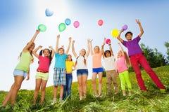 Enfants se tenant avec des bras jusqu'aux ballons de vol Images stock
