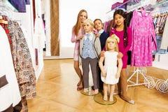 Enfants se tenant avec deux mannequins dans la boutique Images libres de droits