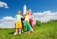 Enfants se tenant en cercle avec la fusée de carton Images stock