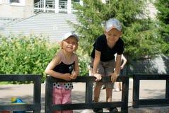 Enfants se tenant sur la barrière Photo stock